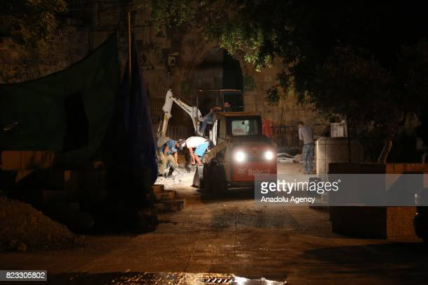 Israeli security forces remove iron guardrails from the AlAqsa Compound in Jerusalem on July 26 2017 While Palestinians immediately celebrated the...