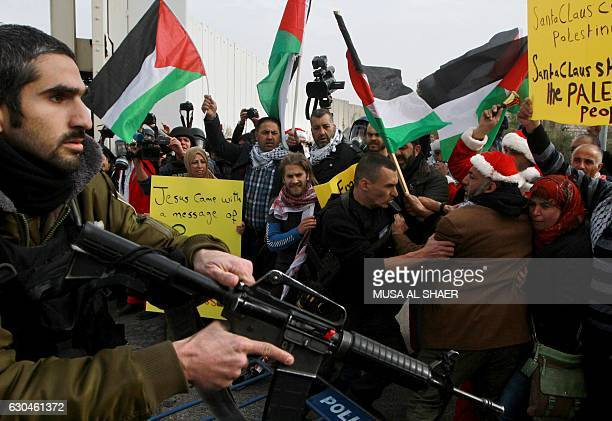 Israeli security forces scuffle with Palestinian protestors some dressed up as Santa Claus during a demonstration next to a gate of a section of...