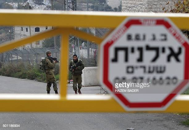 Israeli security forces stand at the site of an attack near the Israeli settlement of Kiryat Arba outside the flashpoint city of Hebron in the...