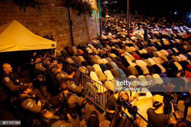 Israeli security forces stand by as Palestinian Muslim worshippers pray outside Lions' Gate a main entrance to the AlAqsa mosque compound in...