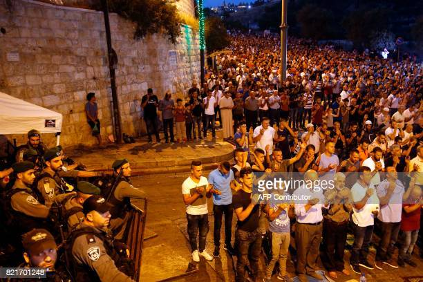 TOPSHOT Israeli security forces stand by as Palestinian Muslim worshippers pray outside Lions' Gate a main entrance to the AlAqsa mosque compound in...