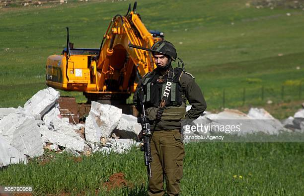 Israeli security forces stand guard as a digger belonging to the Israeli authorities demolishes Salem Abu Ayyash a Palestinian man on the grounds...