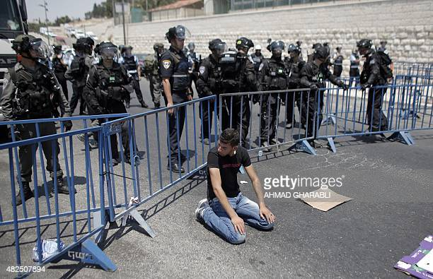Israeli security forces stand guard as a Muslim Palestinian man takes part in Friday noon prayers in the east Jerusalem neighbourhood of Ras alAmud...