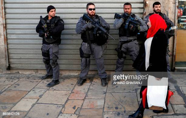 Israeli security forces stand guard as a Palestinian woman walks down a street in Jerusalem on December 16 as demonstrations continue to flare in the...
