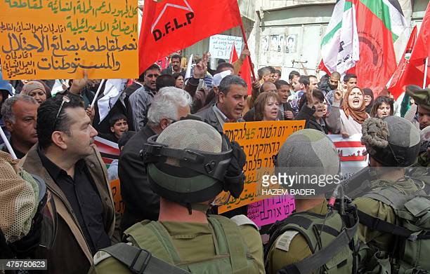 Israeli security forces stand guard as Palestinian protestors hold banner and shout slogans against Israeli settlements and calling for the opening...