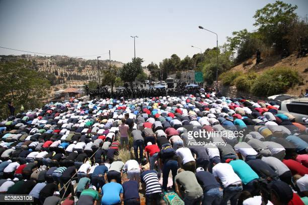 Israeli security forces stand guard as Palestinians Muslims perform Friday Prayer at a security control point near one of the entrances of Al Aqsa...