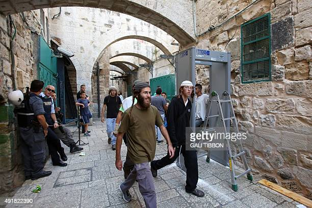 Israeli security forces stand guard as workers install a metal detector in the Muslim quarter of Jerusalem's Old City on October 8 2015 following a...