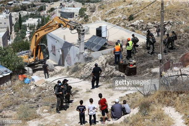 Israeli security forces stand guard at the area as municipal teams demolish the Palestinian Zaatre family's building with bulldozers after Israeli...