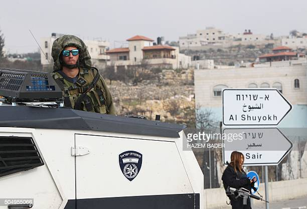 Israeli security forces stand guard at the Beit Einun junction northeast of the West Bank city of Hebron where a Palestinian was shot dead after...