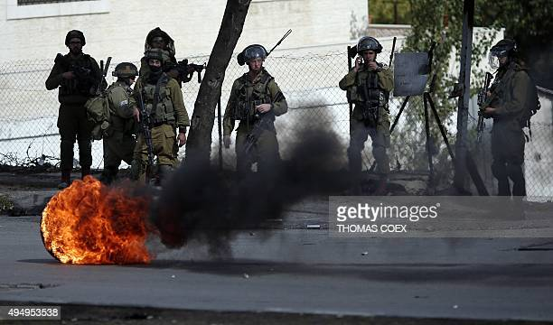 Israeli security forces stand in a street during clashes with Palestinian demonstrators in the West Bank city of Hebron on October 30 2015 Hundreds...