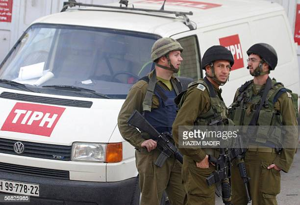 Israeli security forces stand next to the car of the Temporary International Presence in Hebron in the West Bank city as TIPH staff returned 11...