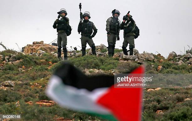 Israeli security forces stand on a hill as a Palestinian man waves the national flag during a demonstration commemorating Land Day in the village of...