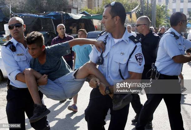 Israeli security forces take a Palestinian child under custody during a protest against Jewish settlers moving into the house of Semasne family after...