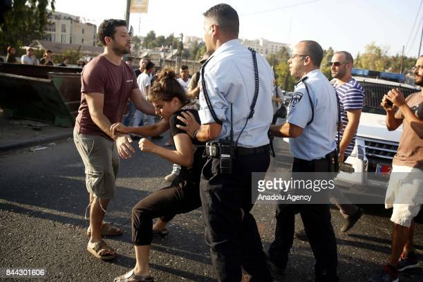 Israeli security forces take a Palestinian girl under custody during a protest against Jewish settlers moving into the house of Semasne family after...