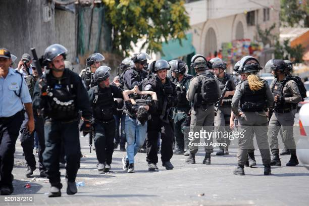 Israeli security forces take a Palestinian into custody as Muslim worshippers perform Friday prayer outside AlAqsa Mosque Compund in Valley of the...