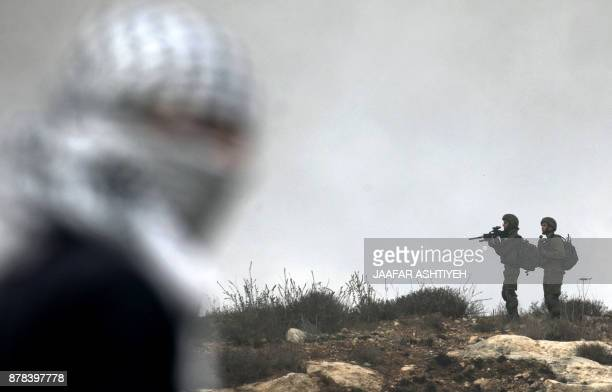 TOPSHOT Israeli security forces take aim as a Palestinian protestor looks on during clashes that followed a weekly demonstration against the...
