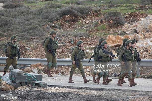 Israeli security forces take measures around the scene after two Israelis were killed and two others wounded in a driveby shooting near the West Bank...