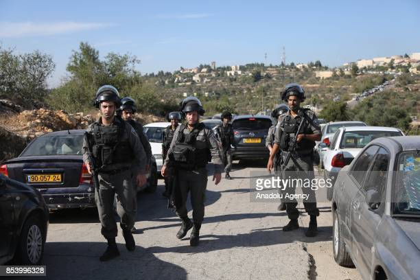 Israeli security forces take security measures at the scene of a shooting attack at the entrance to the Israeli settlement of Har Adar after a...