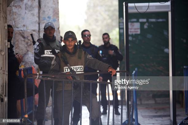 Israeli security forces wait as Palestinians perform prayer near new security metal detectors outside one of the main entrances to the AlAqsa mosque...