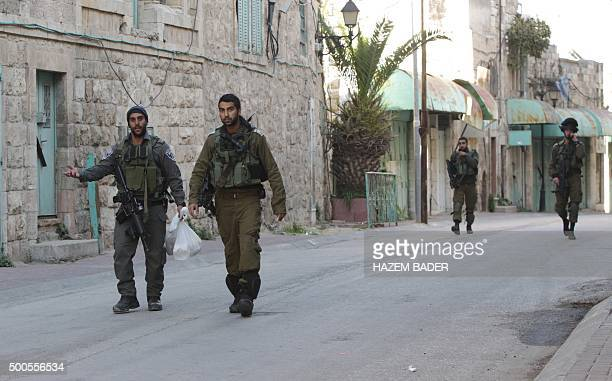 Israeli security forces walk near the site where a Palestinian attacker was shot dead after stabbing two Israelis in the Israeli occupied West Bank...