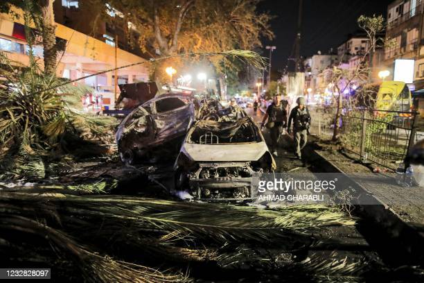 Israeli security forces walk past extinguished burnt vehicles in Holon near Tel Aviv, on May 11 after rockets were launched towards Israel from the...