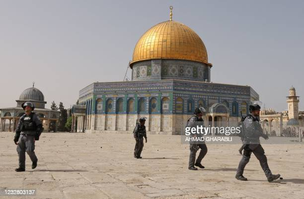 Israeli security forces walk past the Dome of the Rock as they clear the grounds of Jerusalem's Aqsa mosque compound from Palestinian protesters on...