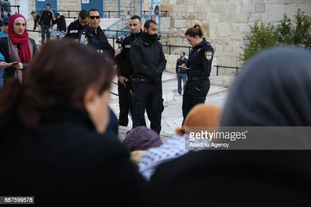 Israeli security members stand guard as Palestinian demonstrators gather near the Damascus Gate during a protest against the US President Donald...