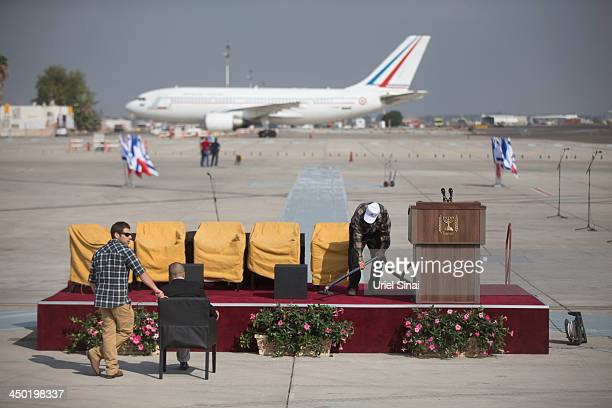 Israeli security personal guard as a worker cleans the stage ahead of the arrival of French President Francois Hollande at the Ben Gurion...