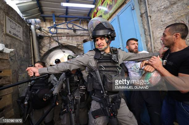 Israeli secutiry forces block access to Palestinian demonstrators during protests against Israel's occupation and its air campaign on the Gaza strip,...