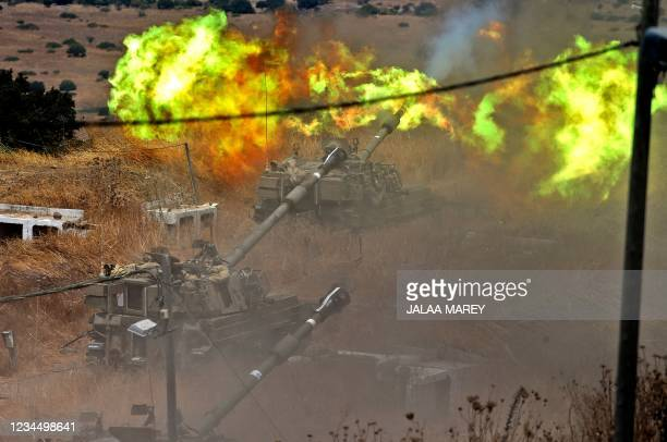 Israeli self-propelled howitzers fire towards Lebanon from a position near the northern Israeli town of Kiryat Shmona following rocket fire from the...