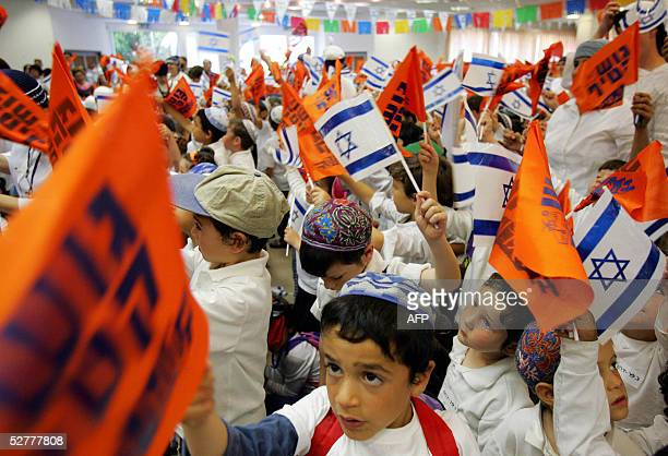 Israeli settler children wave Israeli and Gush Katif flags during a ceremony to mark the upcoming Israeli Independence day in the settlement of Neve...