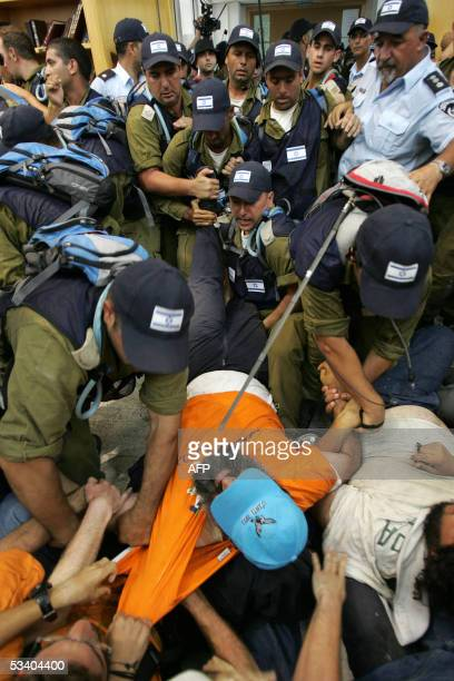 Israeli settlers are evacuated from the synagogue of the southern Gaza Strip settlement of Neve Dekalim 18 August 2005 Israeli police dragged dozens...