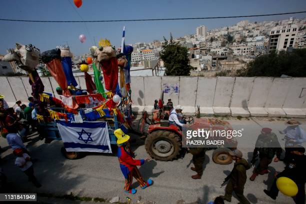 Israeli settlers celebrate the Jewish Purim holiday at alShuhada street in the divided West Bank town of Hebron on March 21 2019 The carnivallike...