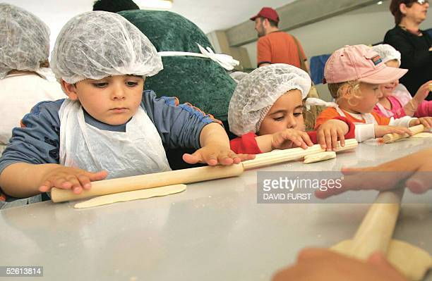 Israeli settlers' children prepare Matza a traditional bread for the upcoming Jewish holiday of Passover in the Israeli settlement of Neve Dekalim...