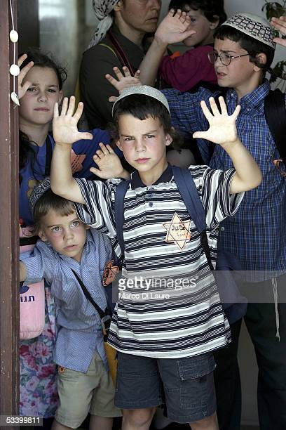 Israeli settlers children with the Star of David pinned to their shirts raise their hands prior to being removed August 17 2005 in the Morag...