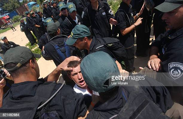 Israeli settlers from the Gaza Strip settlement of Neve Dekalim scuffle with border guards as they try to block the access to trucks carrying moving...
