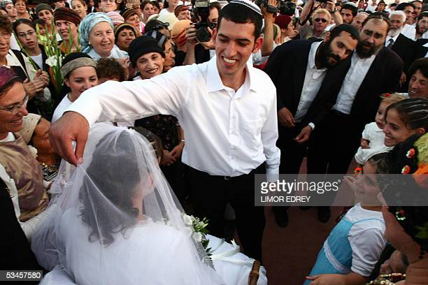 Israeli settlers gather aroud newlywed couple Bezalel and Rivka Weinstein during their wedding celebration at the Faith City encampment on the...