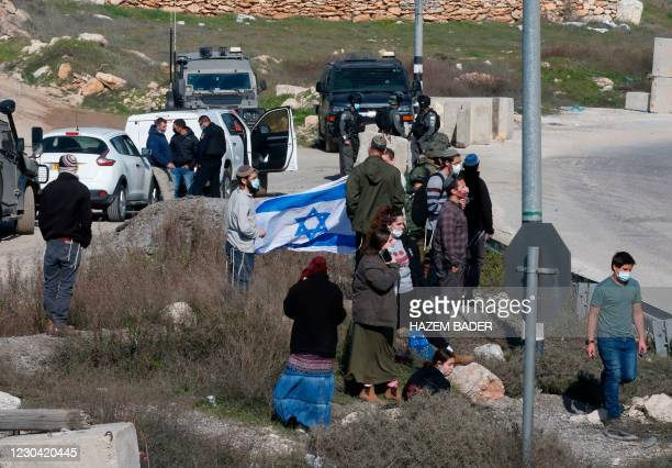 Israeli settlers gather at a junction with security forces arriving to block Palestinians trying to reach their lands confiscated by Israeli...