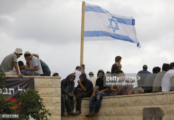 Israeli settlers gather next to their national flag on a rooftop of a house at Netiv Haavot settlement near Bethlehem, in the occupied West Bank on...