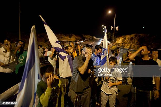 Israeli settlers pray and hold flags on June 30 2014 at the enterence to Halhoul north of Hebron West Bank The bodies of three Israeli teenagers who...