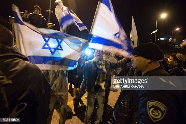 TOPSHOT Israeli settlers protest outside their settlement of Kiryat Arba in the southern West Bank after a suspected Palestinian attacker stabbed to...