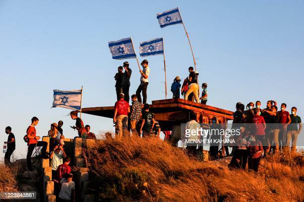 TOPSHOT Israeli settlers some maskclad due to the COVID19 coronavirus pandemic gather on a hill next to the Palestinian town of Halhul north of...