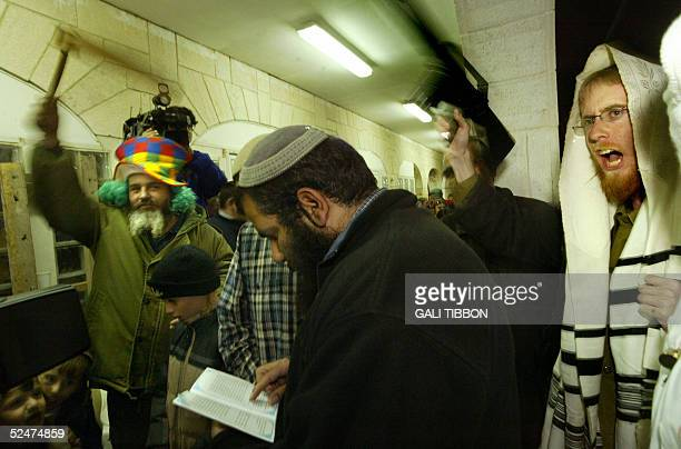 Israeli settlers some wearing Purim costumes use toy guns and a rattle to make noise while listening to the traditional reading of the scroll of...