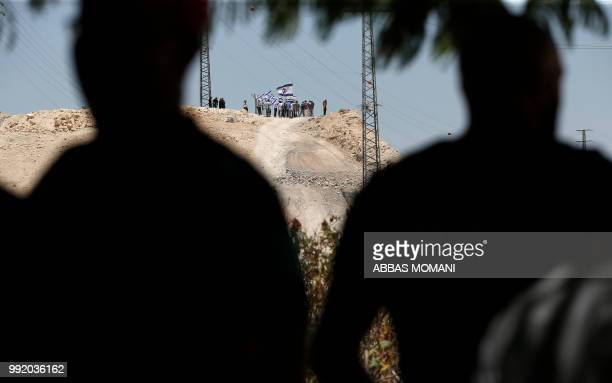 TOPSHOT Israeli settlers wave their national flag on a hill overlooking the Palestinian Bedouin village of Khan alAhmar east of Jerusalem in the...