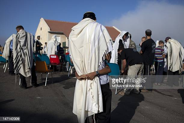 Israeli settlers wrapped in a tallit or prayer shawl is hugged by a child as he prays in front of houses in the Ulpena neighbourhood of Beit El...