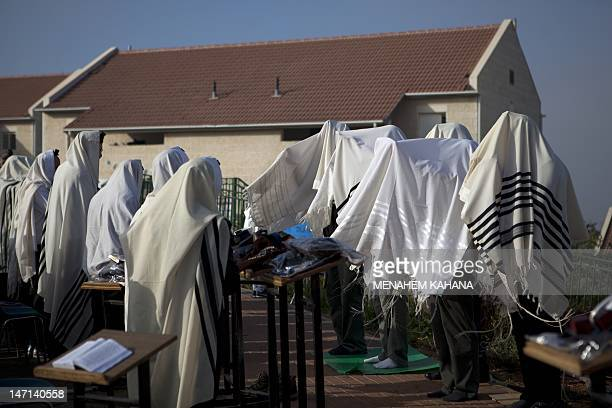Israeli settlers wrapped in a tallit or prayer shawl pray in front of their houses in the Ulpena neighbourhood of Beit El settlement in the Israeli...