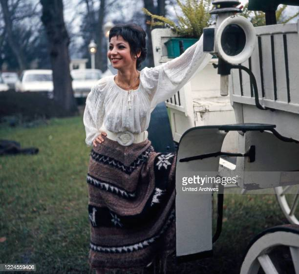Israeli singer and actress Esther Ofarim poses in front of a white coach circa 1969