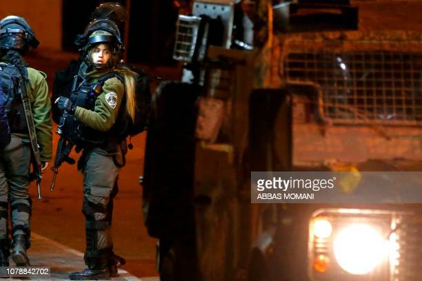TOPSHOT Israeli soldier clash with Palestinian youth during an incursion into the West Bank city of Ramallah on January 7 2019