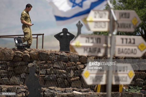 Israeli soldier is seen next to a signs pointing out distance to different cities on Mount Bental next to the Syrian border on May 10 2018 in the...