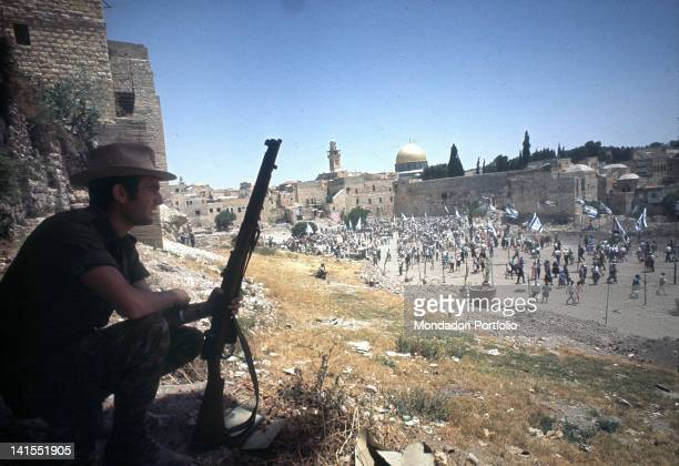 Israeli soldier on guard duty looking at the celebrations by the Western Wall for the end of the ArabIsraeli SixDay War Jerusalem June 1967